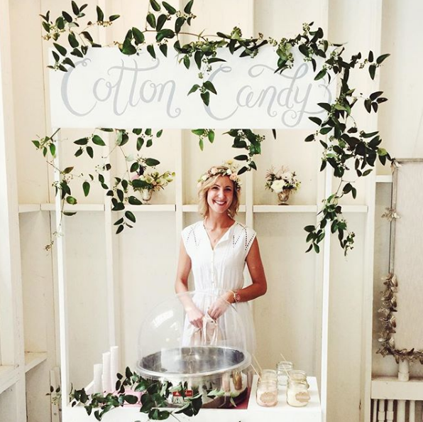 Woman in white manning a cotton candy station at an event as an engagement party idea