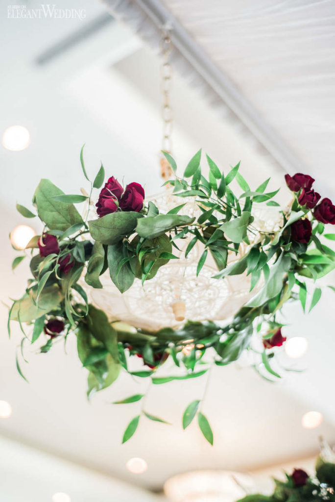 Garland of flowers and leaves around light fixture as an idea for bridal shower decorations