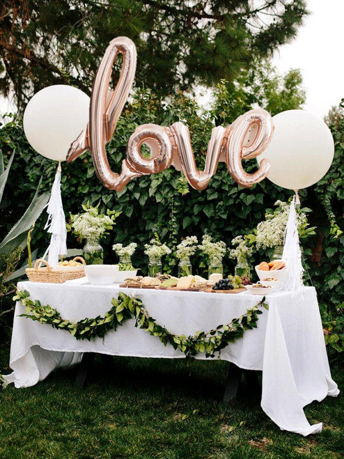 Balloon shaped like the word Love over a festive table as an engagement party idea