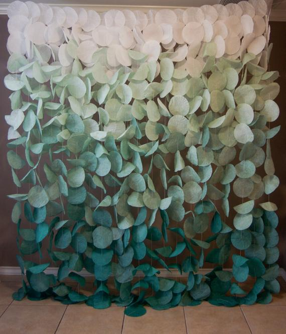 hanging backdrop of ombre green as an idea for bridal shower decorations