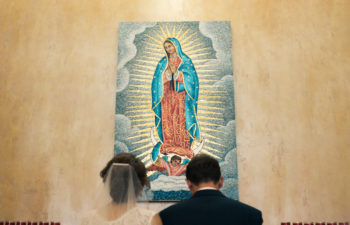 A couple in a wedding dress and a dark suit kneel in prayer in front of a image of Our Lady of Guadalupe