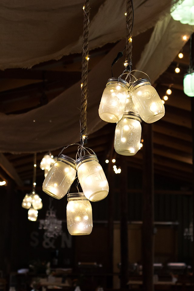 Strands of mason jars filled with fairy lights as an idea for bridal shower decorations