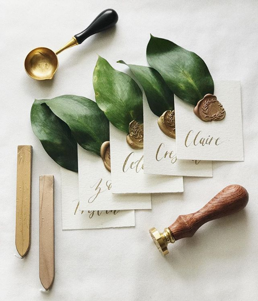 Place cards with calligraphy lettering, wax seals, and leaves as an idea for bridal shower decorations
