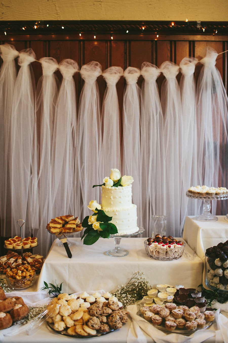 Long swaths of white tool strung as tassels across a white cord serve as backdrop for a dessert table piled with cookies and other treats with a tiered white cake as an idea for bridal shower decorations
