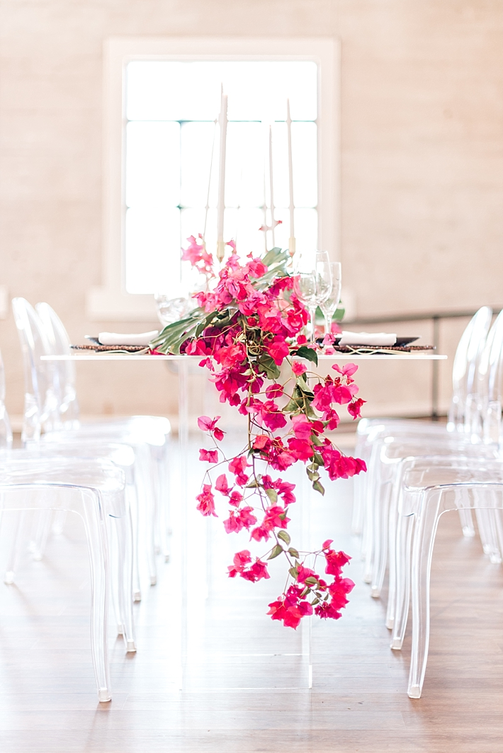 Table with clear chairs and pink shower of flowers as an idea for bridal shower decorations
