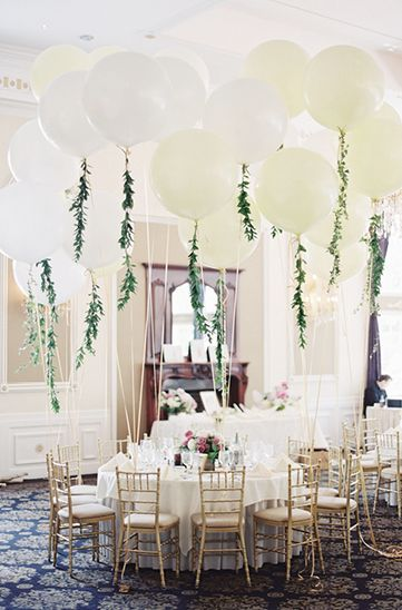 bridal shower decorations - banquet hall filled with tables and balloons with garlands of leaves