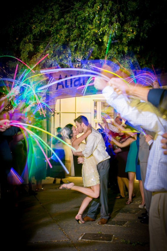 Guests wave glowsticks around dancing couple