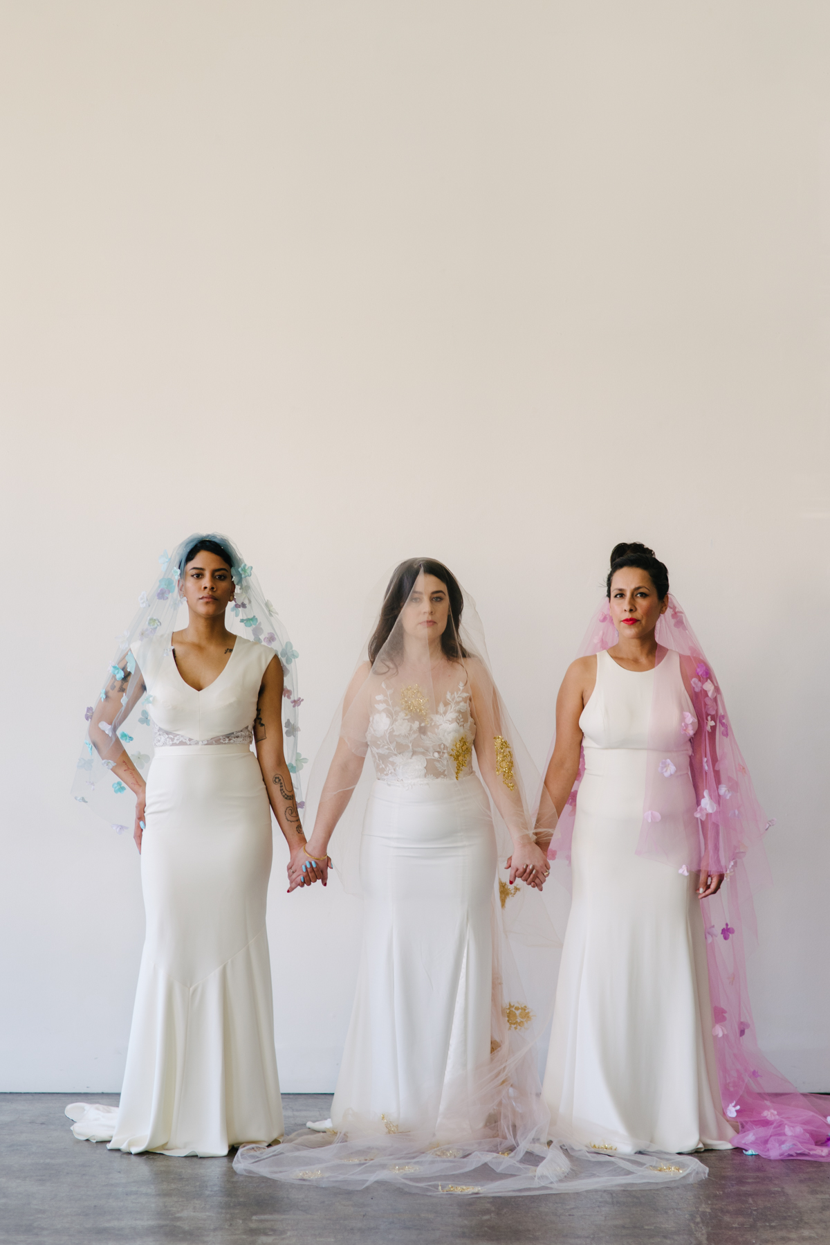 Three women stand side by side holding hands while wearing different color wedding veils