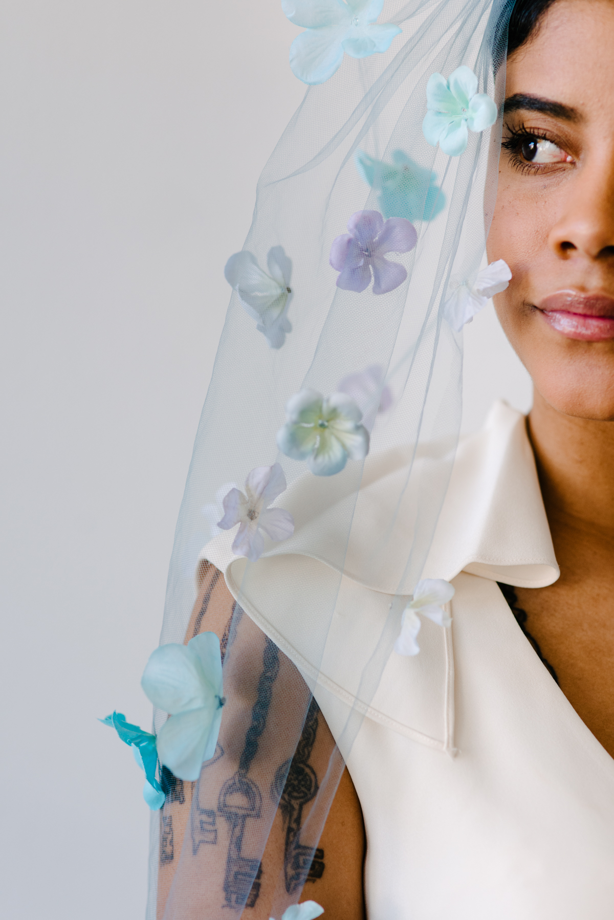 Close up of a wedding veil dyed light blue with colorful flowers attached