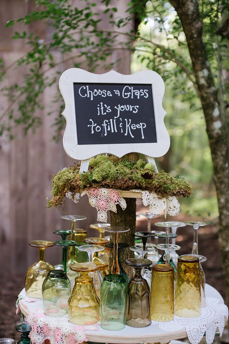 Table of glassware with sign in the woods.