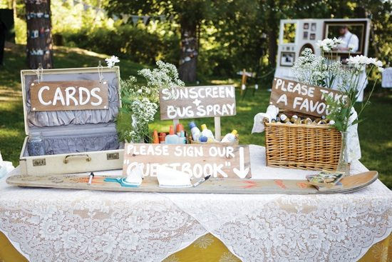 Welcome table at wedding with cards and sunscreen and favors boxes