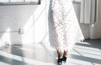 the back of a woman wearing a short wedding dress and heels from the waist down