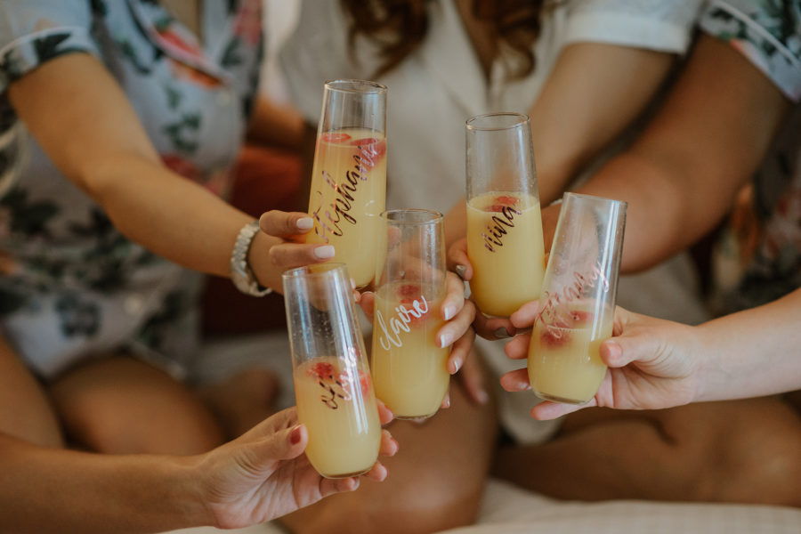Womxn in matching pjs toast mimosas in stemless champagne glasses with their names written in gold calligraphy on them