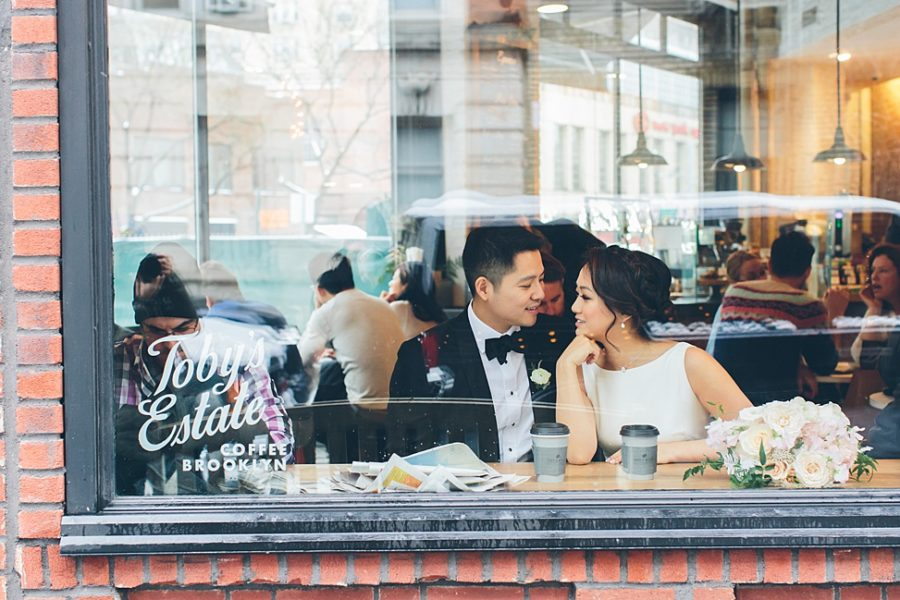 A wedding couple sit inside a cafe, lovingly looking at each other.