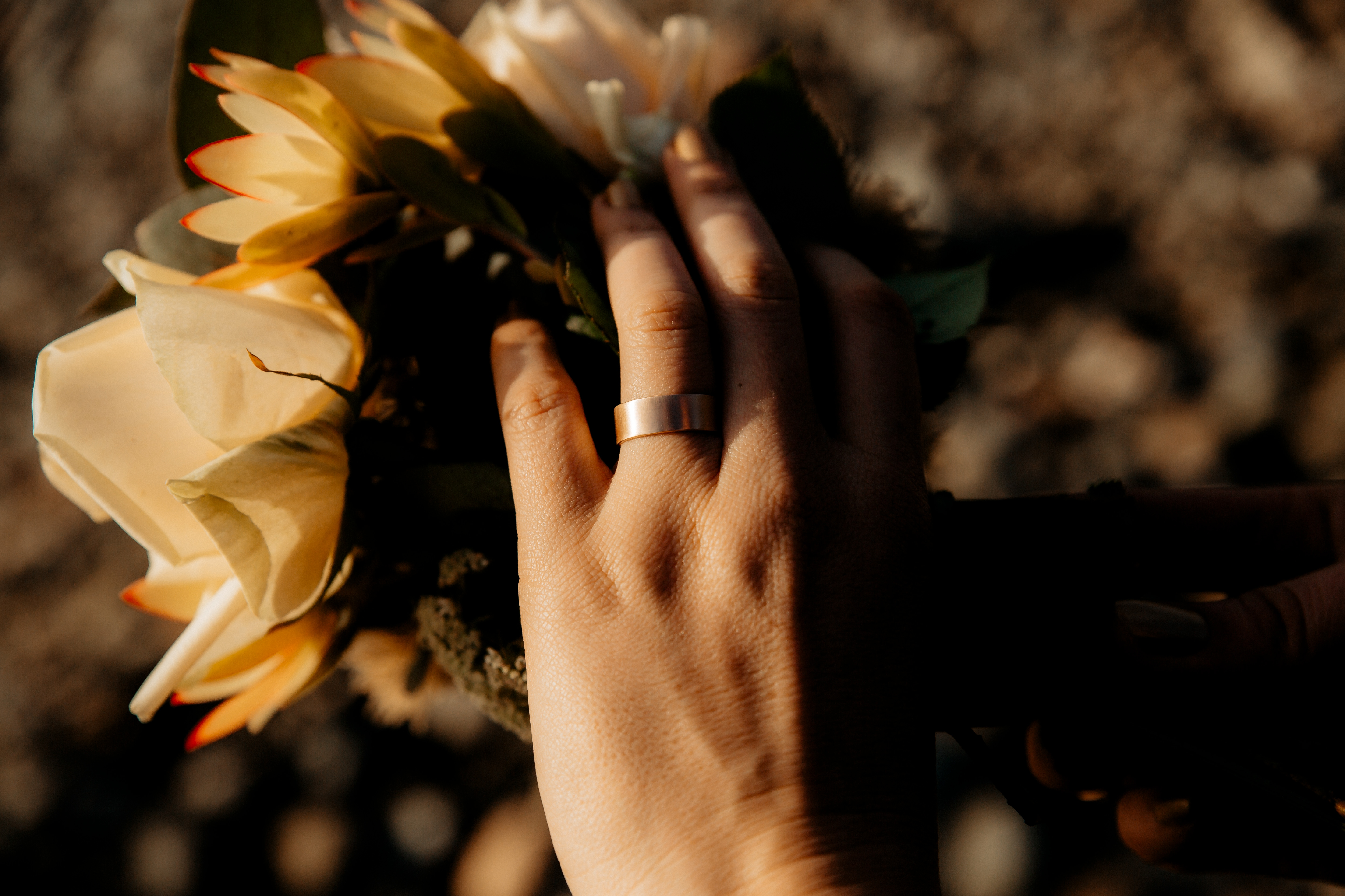 Closeup of a hand lightly touching a flower, wearing a Good Gold wedding band