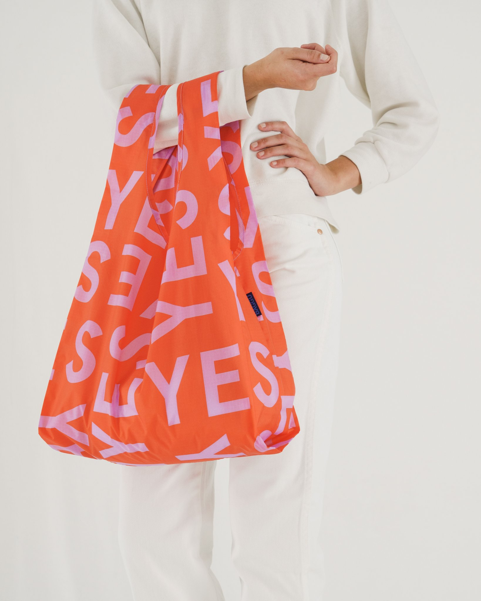 Woman in white holding reusable orange bag with the word YES on it for bridal shower favors