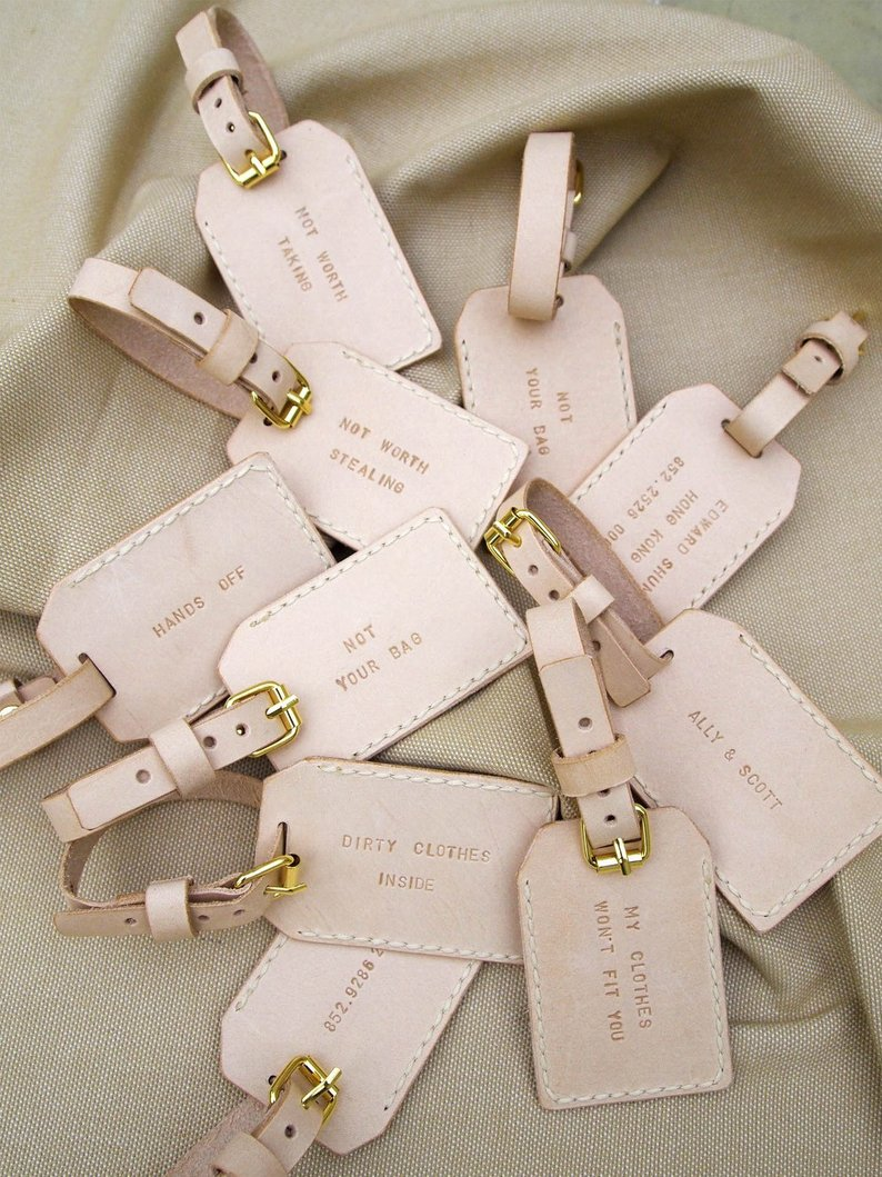 Light pink leather luggage tags and stamped with fun phrases for bridal shower favors