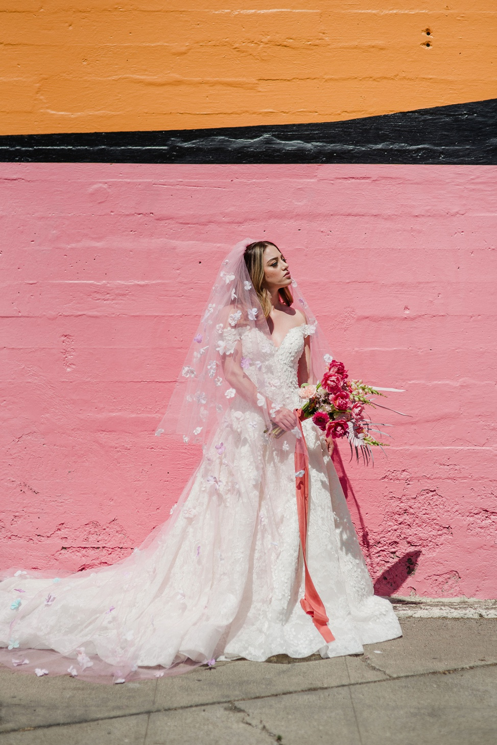 A woman wears allure couture style c520 while standing against a pink and orange wall holding a pink bouquet and wearing a pink veil with floral appliques
