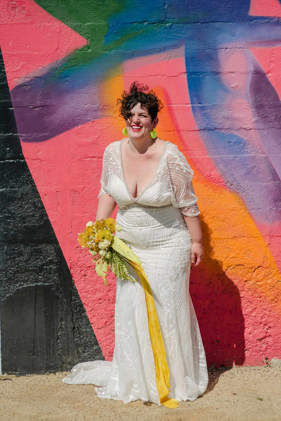 a plus size bride laughing against a bright mural wearing a madison james gown and holding a bright yellow bouquet with flowing yellow ribbon and wearing yellow fringe earrings