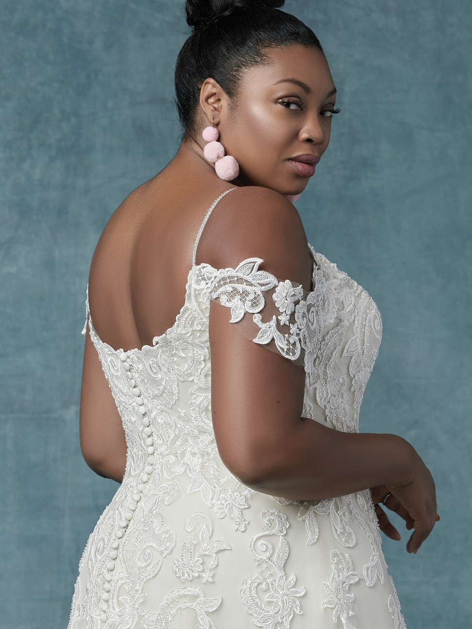 a plus size black bride wears the sorrento lynette gown with off-the-shoulder lace from maggie sottero designs