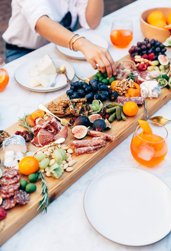 A centerpiece made up of a table running wooden board covered with cured meats, fruits, and cheeses