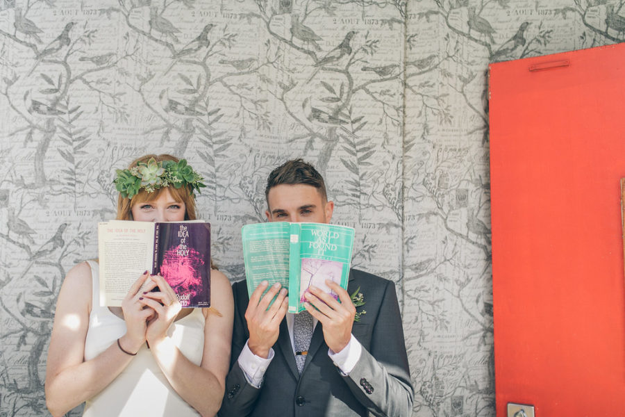 Two people hold books up to their faces, books with wedding readings in them.