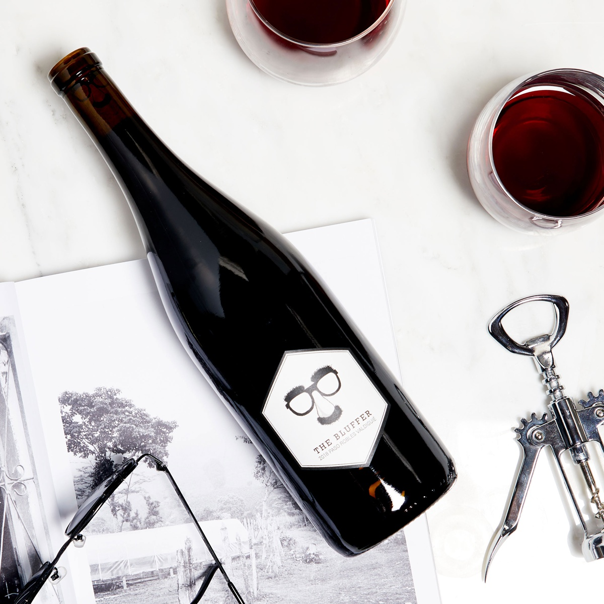 a bottle of Winc's bluffer valdiguié styled in a lay flat on a white surface with a corkscrew, two glasses of red wine, a pencil illustration and a pair of sunglasses