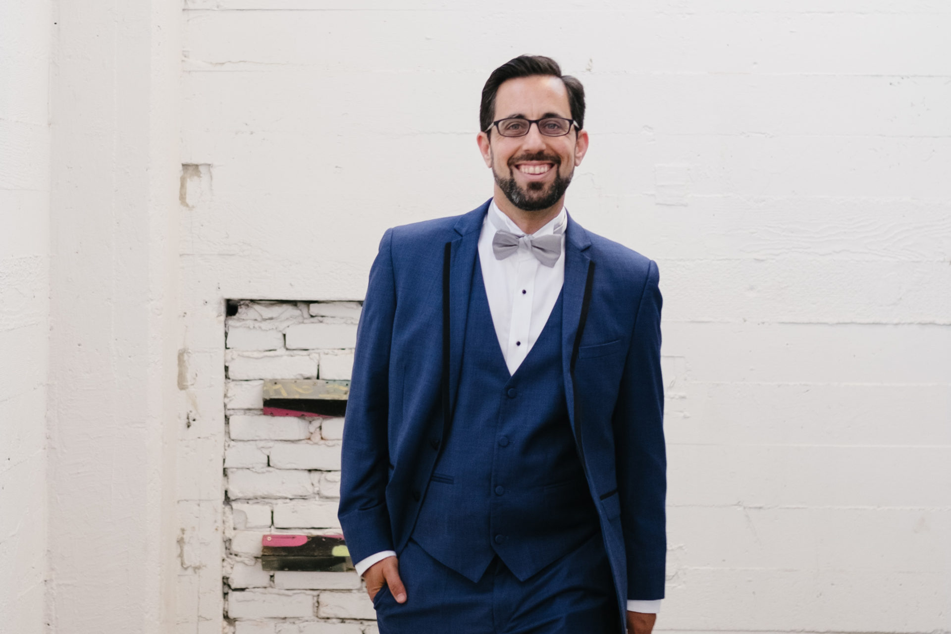 a man smiles while walking in front of a white industrial wall wearing a mystic blue wedding tuxedo from generation tux