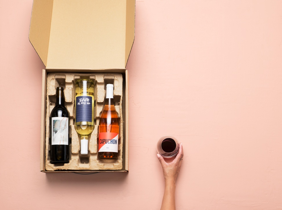 An open mailing package of Winc wine
