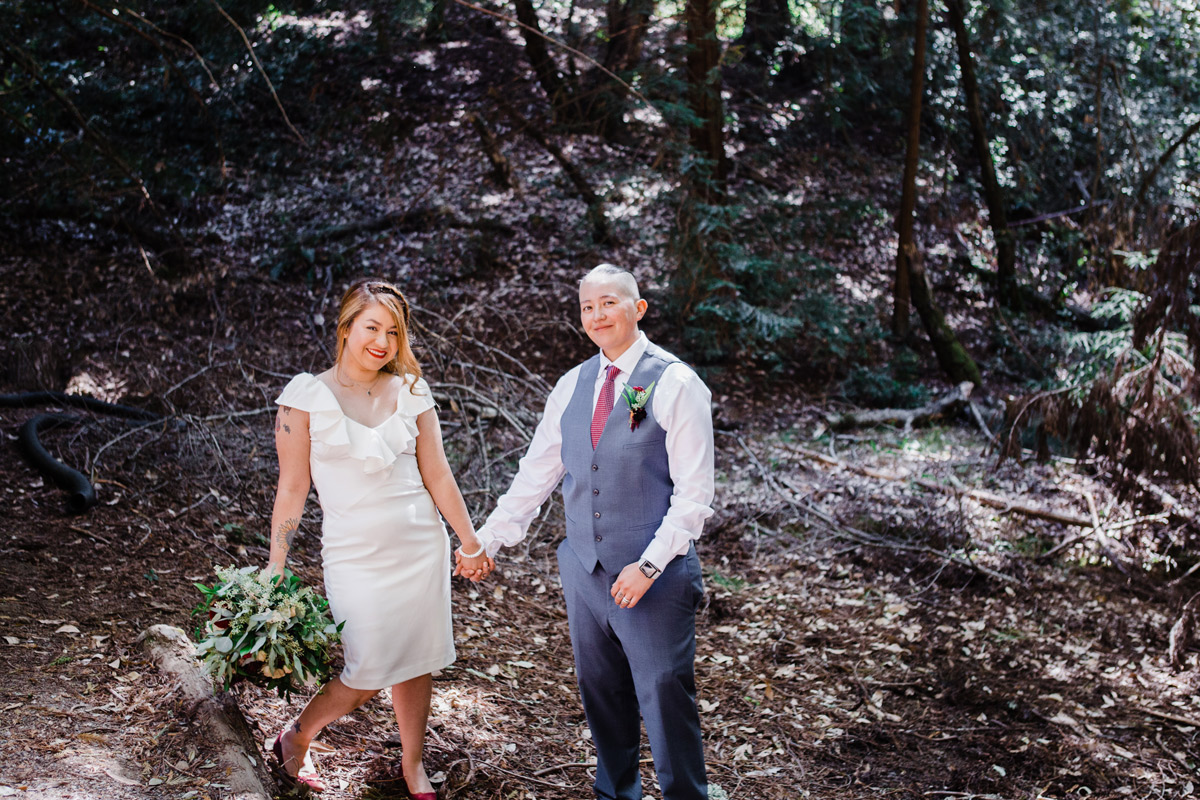 A wedding couple hold hands in the woods