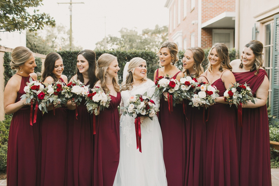 A bridal party stand together wearing deep red bridesmaid dresses
