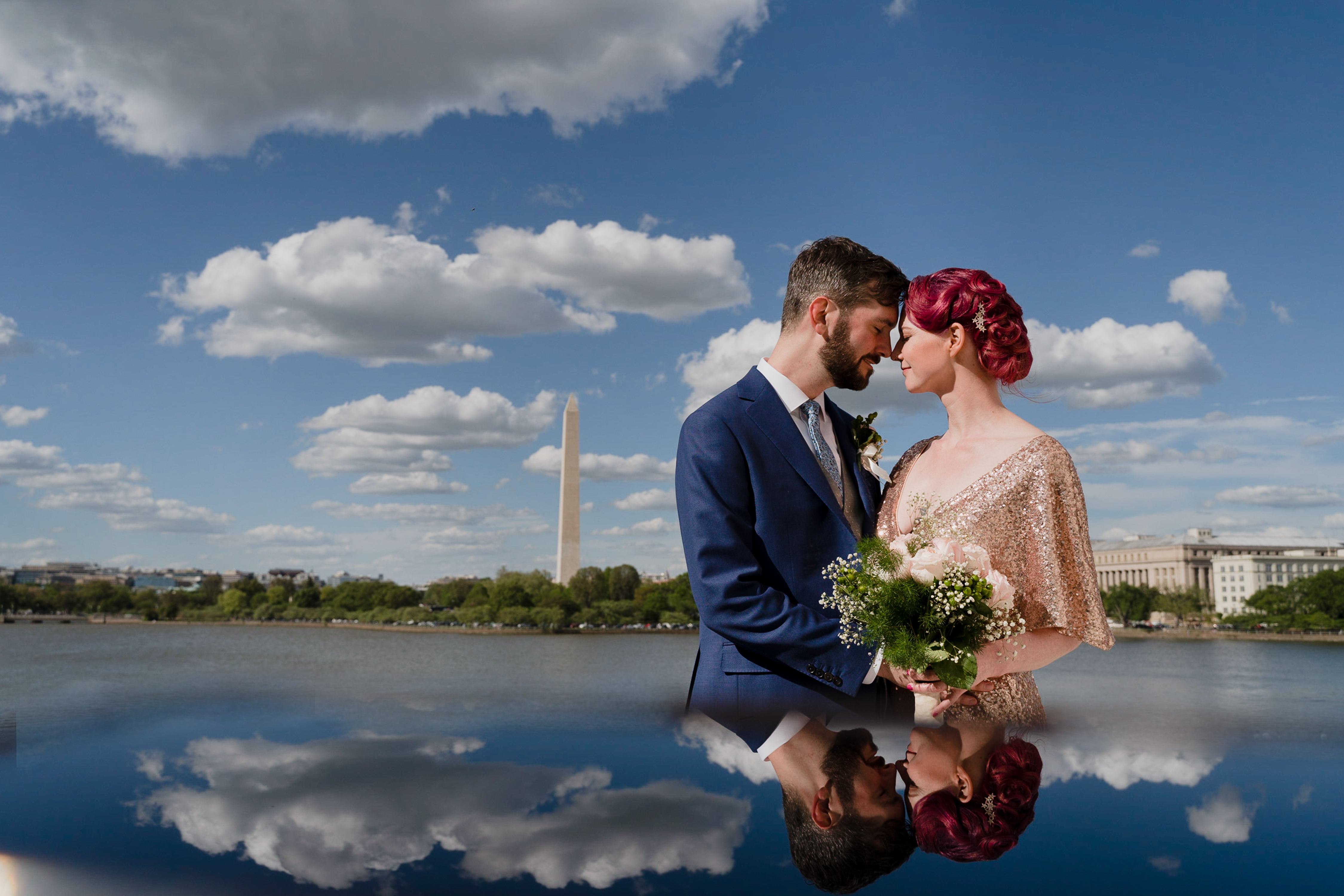 A wedding couple touch forehands gently with the Washington Monument in the background