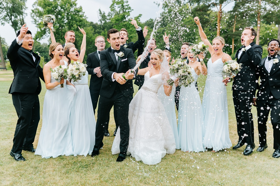 An entire wedding party cheer as champagne is bursting from a bottle