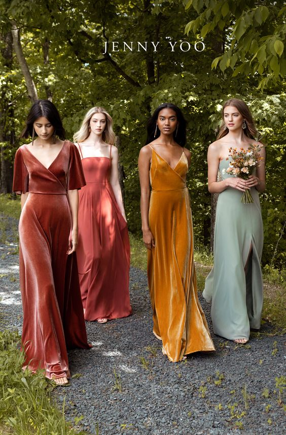 Four models walk down a path wearing dresses in fall wedding colors