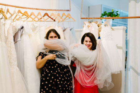 Two women swathed in tulle at a bridal shop