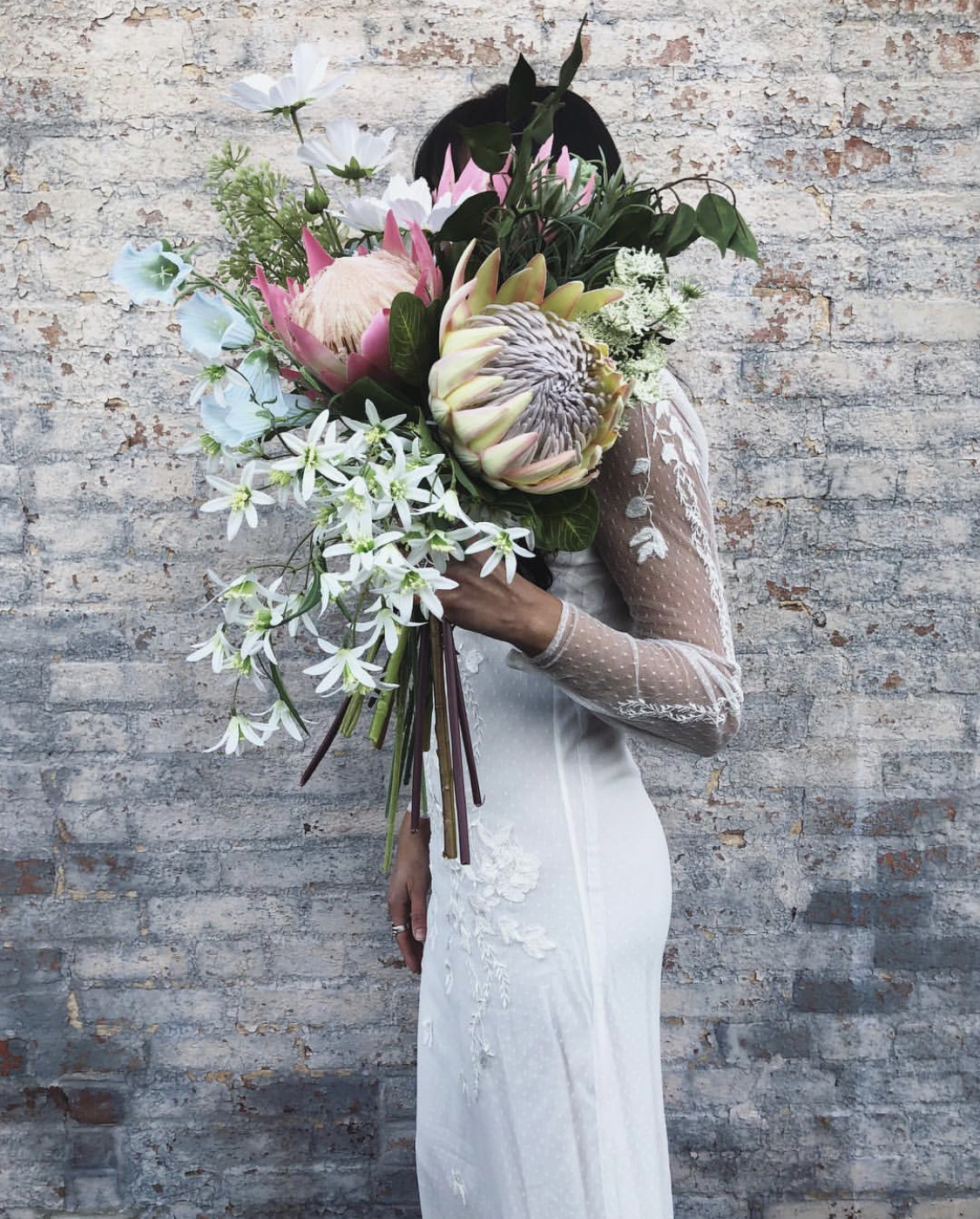 Woman in white dress holds large bouquet of fake wedding flowers in front of a brick wall