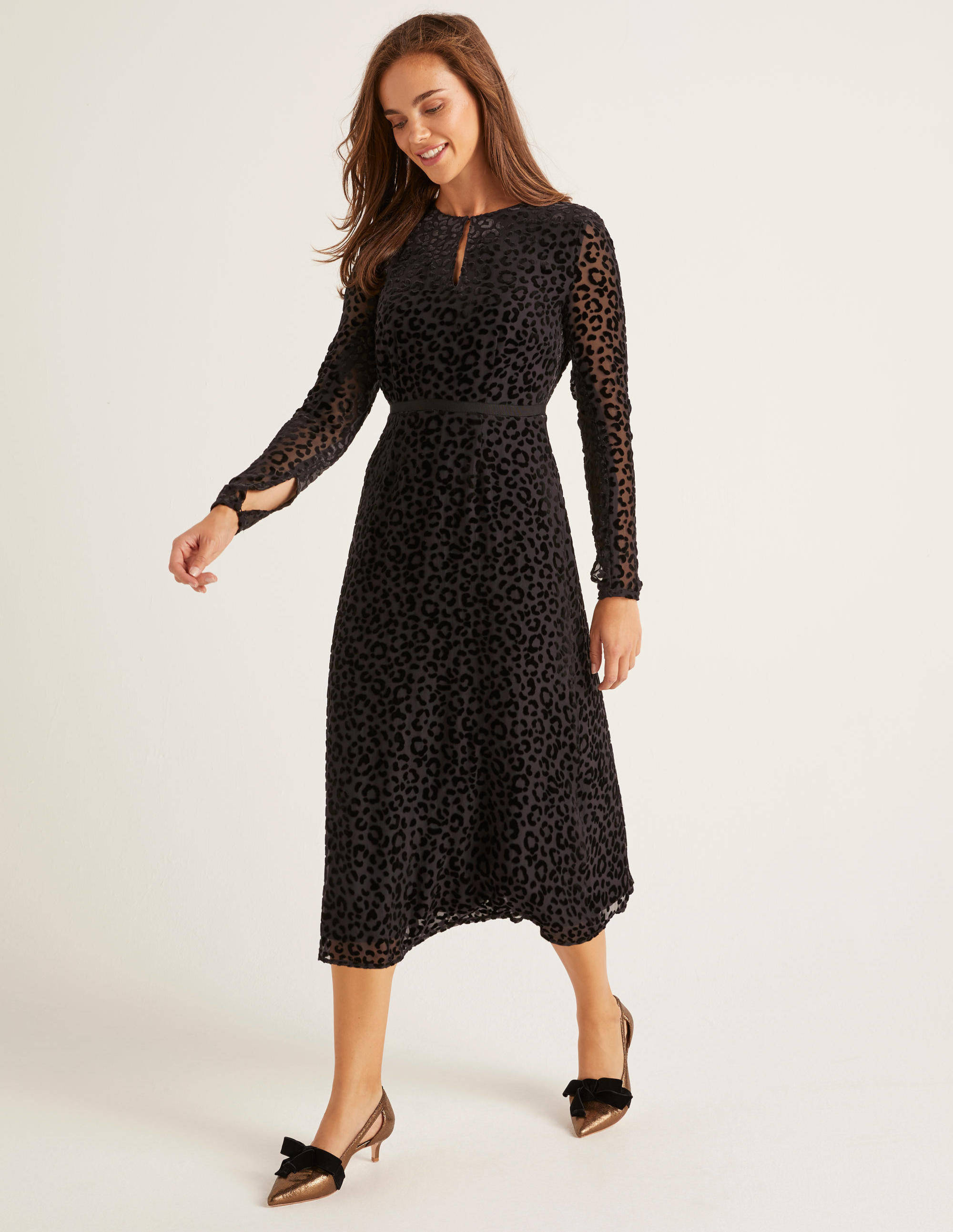 A model wears a dress described as being Crafted from silky viscose and covered in velvety leopard print, this on-trend midi dress is a statement staple.