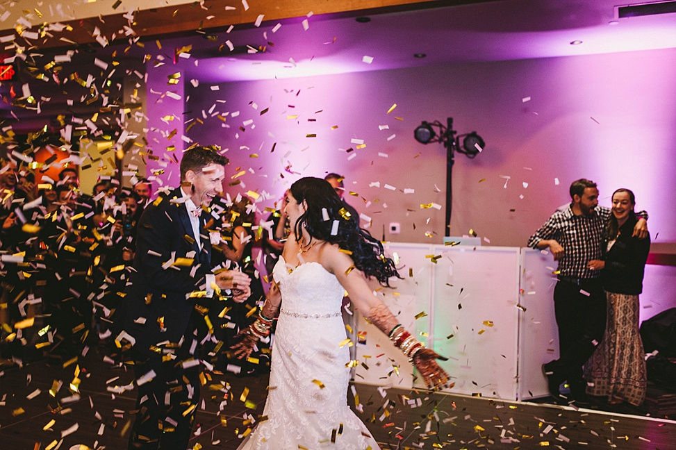 A couple dance on the dance floor as confetti falls from the ceiling.