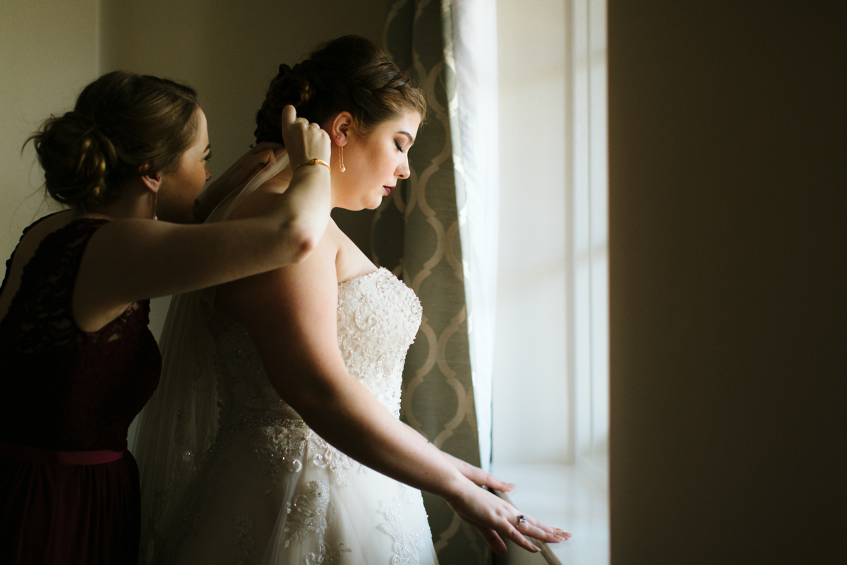 A bride stands at a window as another woman inserts her wedding veil.