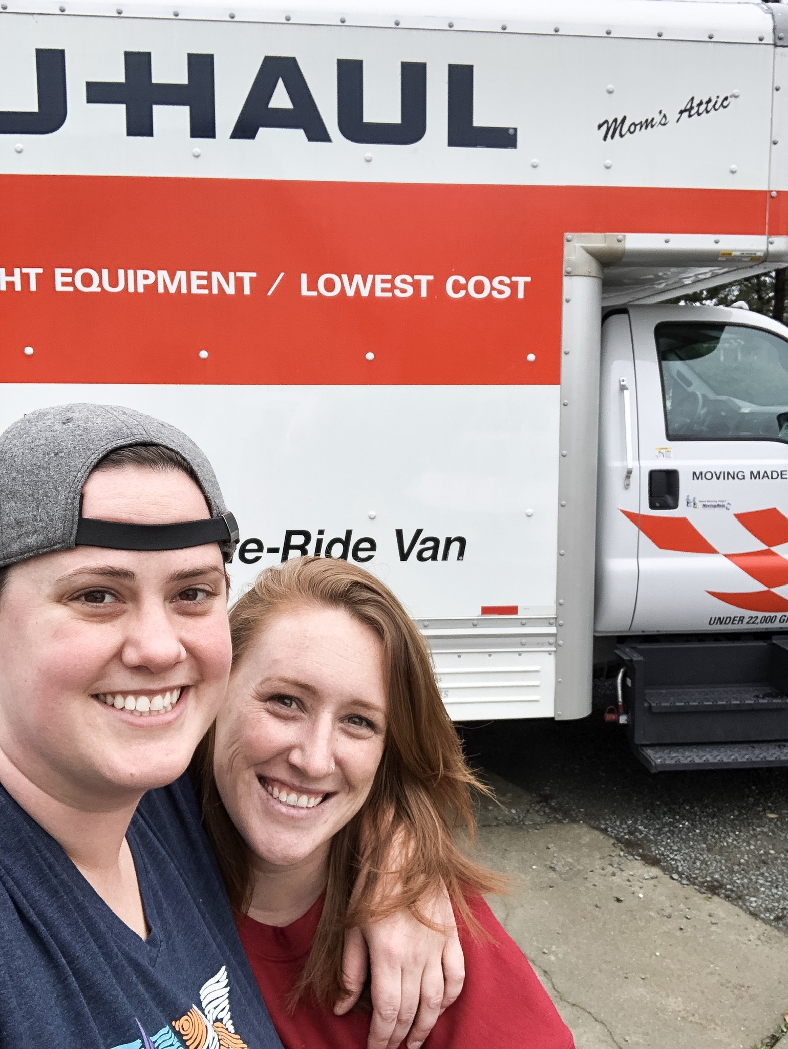 A photo of a couple standing in front of a uhaul truck.
