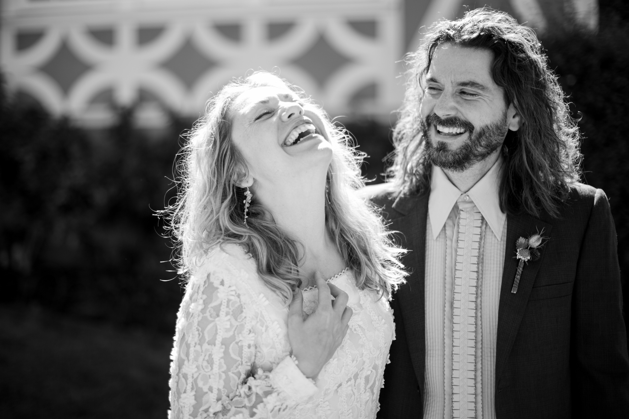 A wedding couple laugh together.