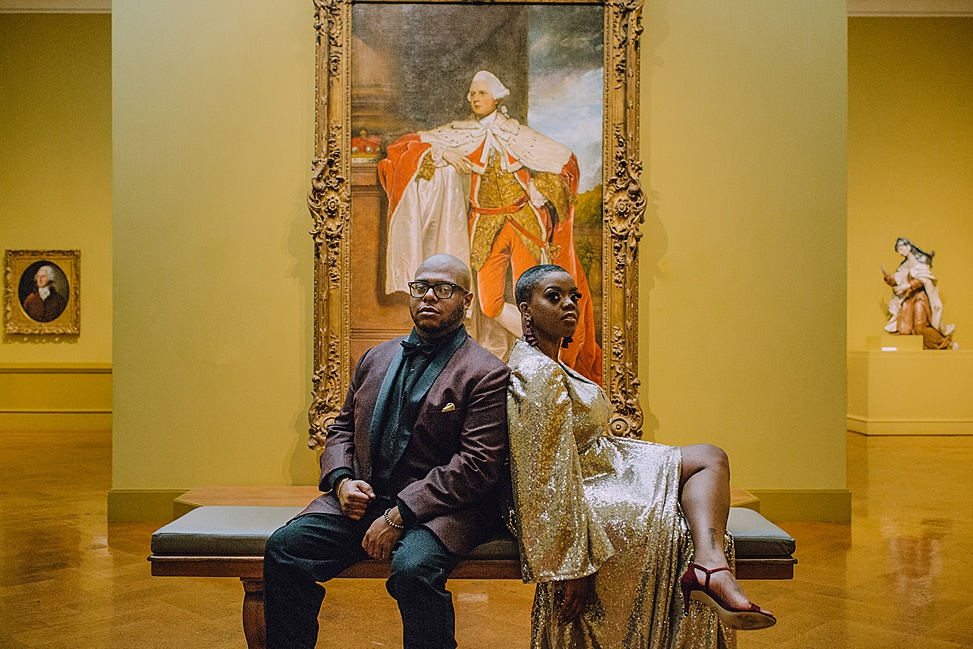 A wedding couple sit in front of art.