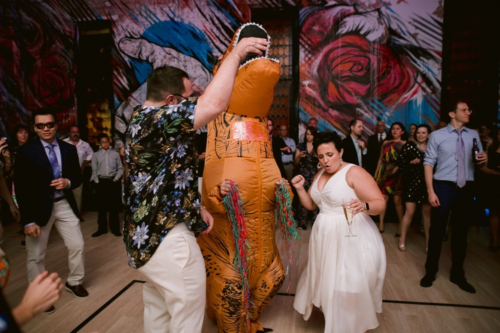 A wedding couple dance during their reception with a T-Rex