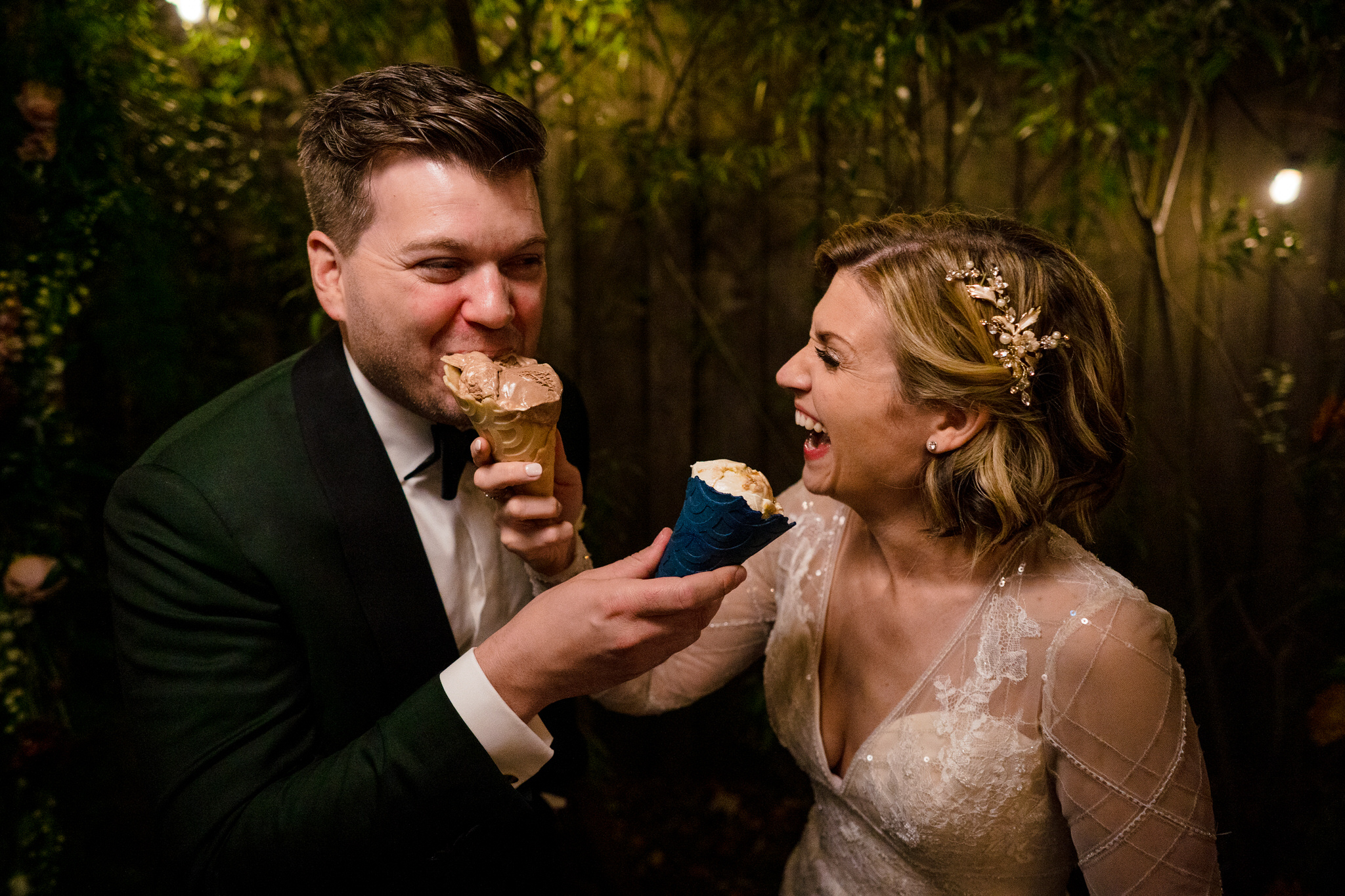A wedding couple smile and eat ice cream cones.