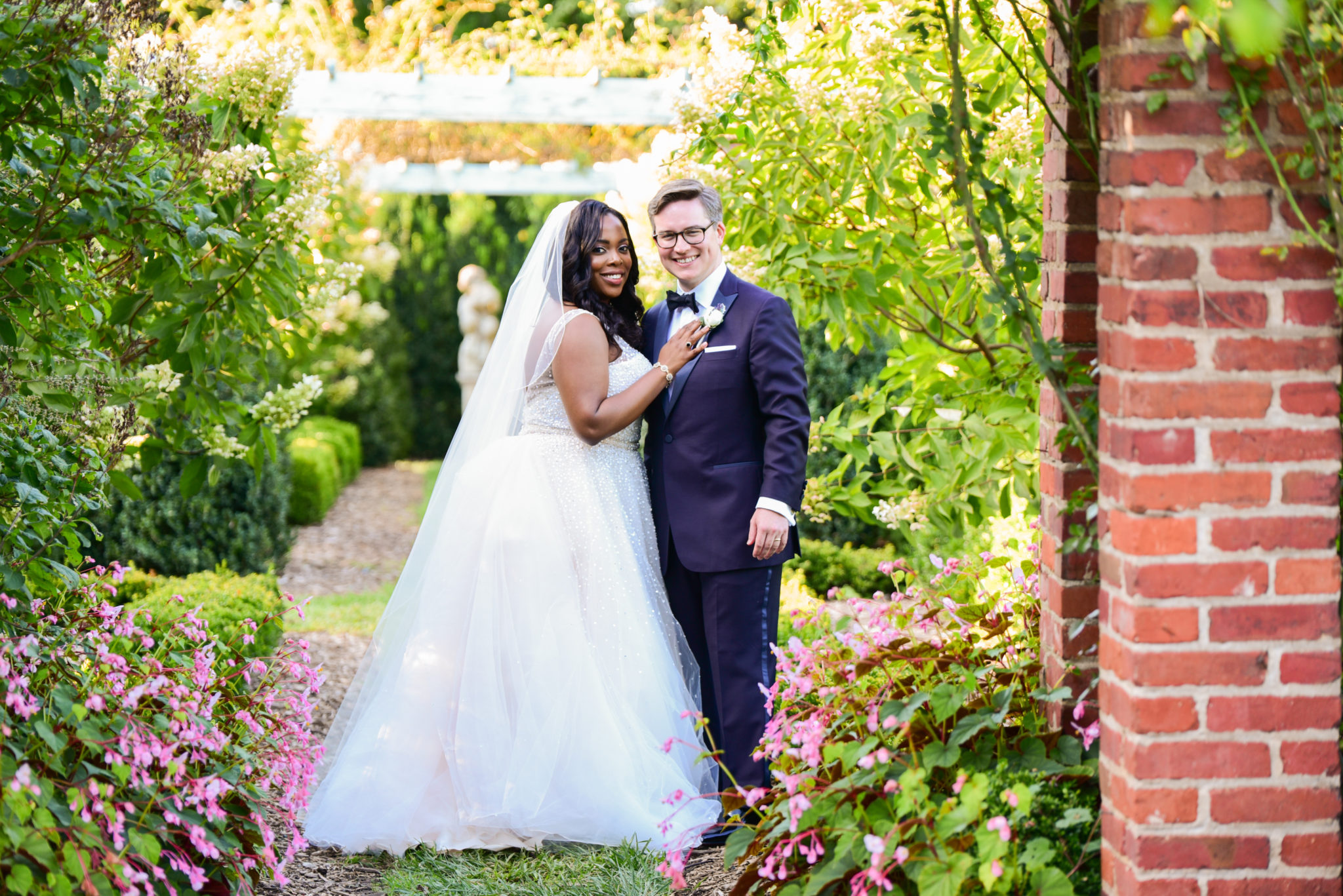 A wedding couple stand and smile on a garden walkway.