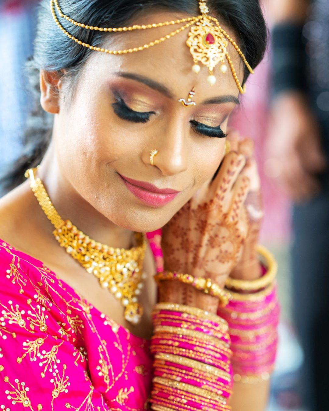 A bride smiles as she puts on an earring.