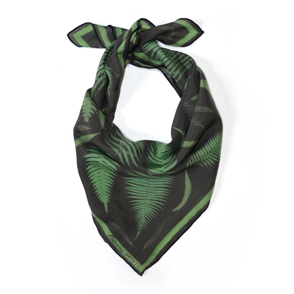 A scarf with fern leaves printed on it.