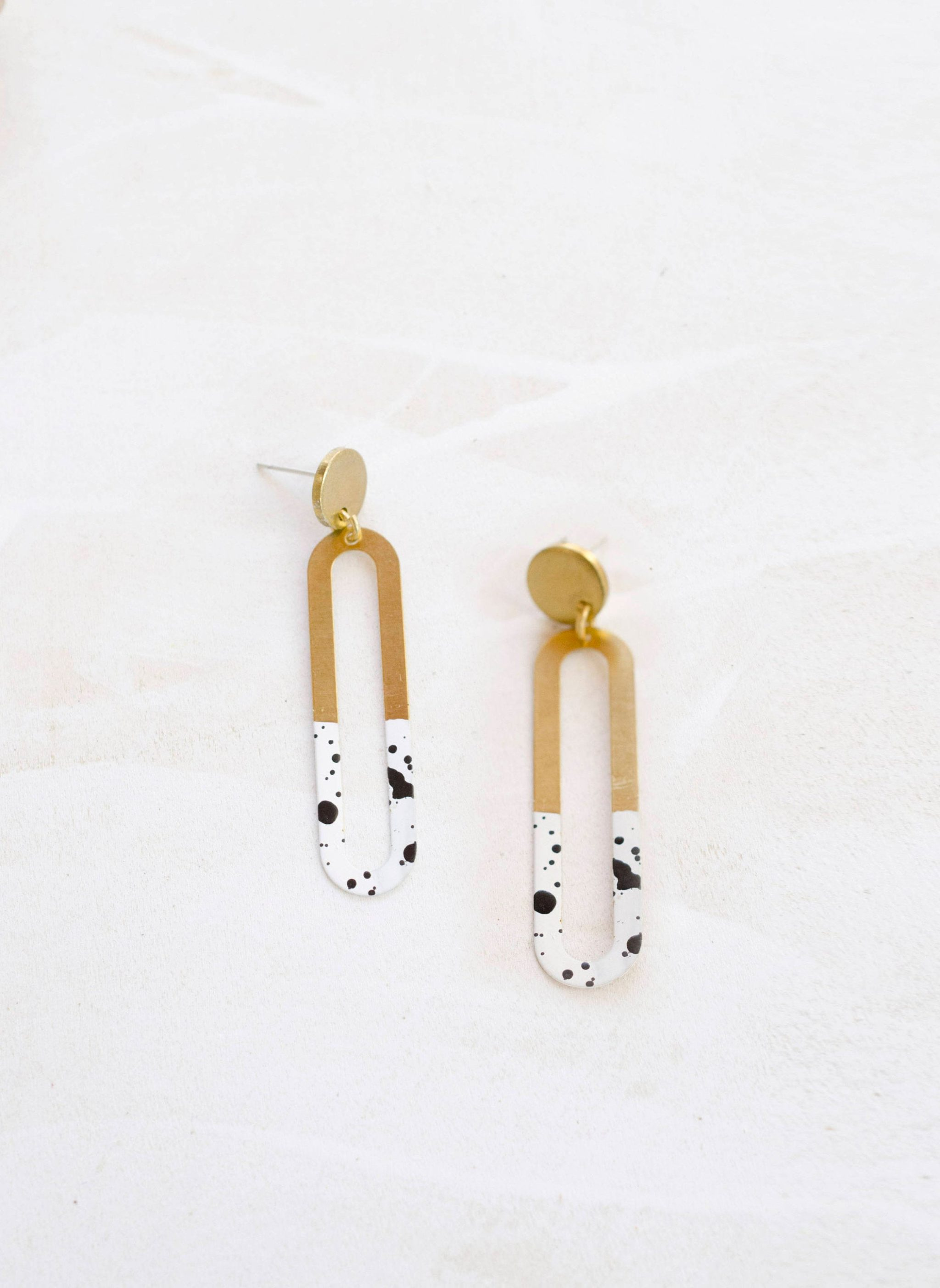 Earrings that are half brass and half speckled pattern.