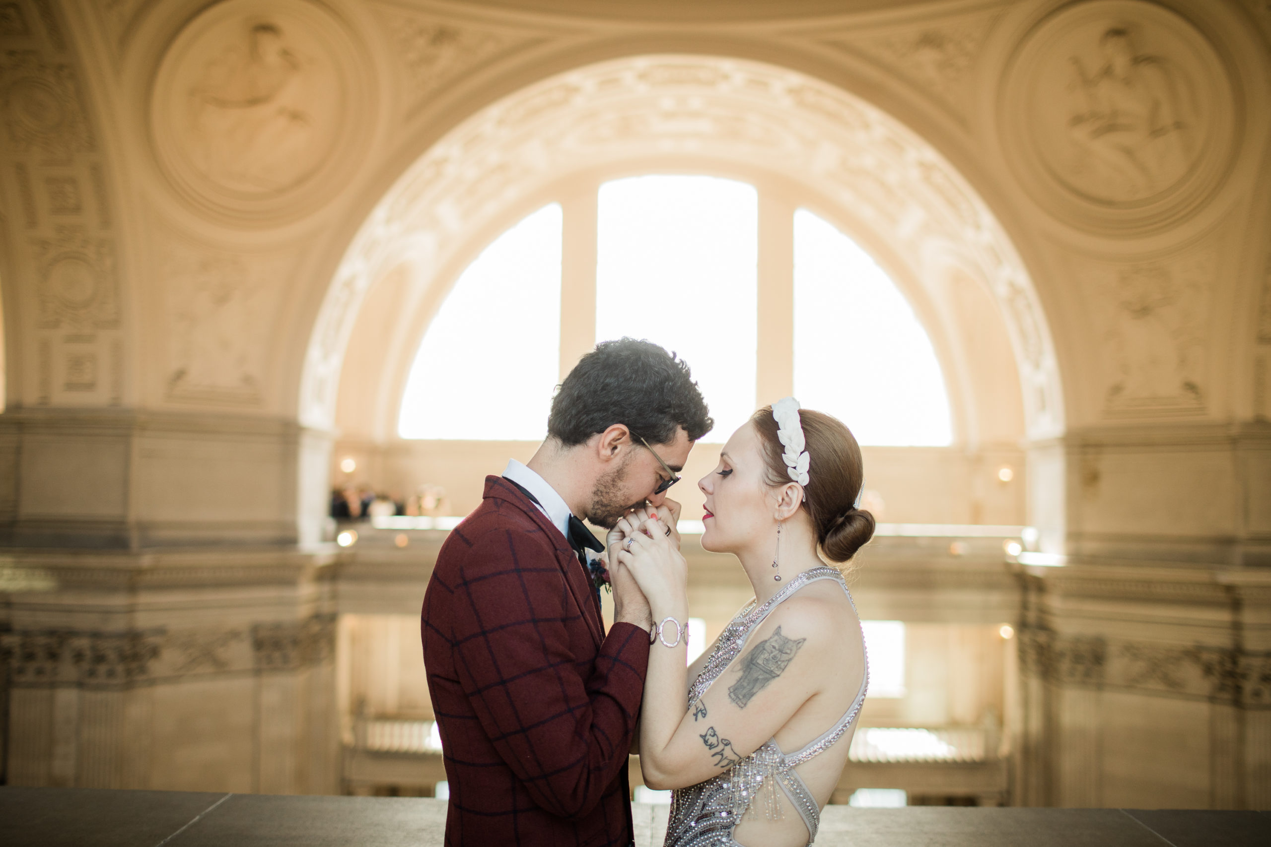 A wedding couple hold hands and kiss while at City Hall.