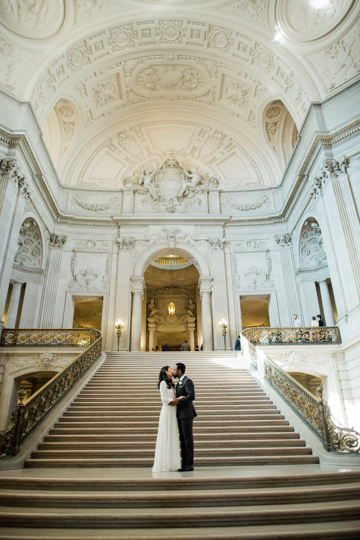A wedding couple kiss while standing on steps in City Hall